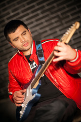 Handsome musician playing rock and roll the electric guitar