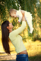 Happy mother and baby playing outdoors.