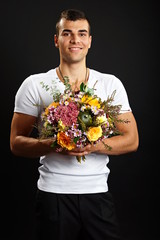 Young smiling man in white shirt holds bouquet of flowers