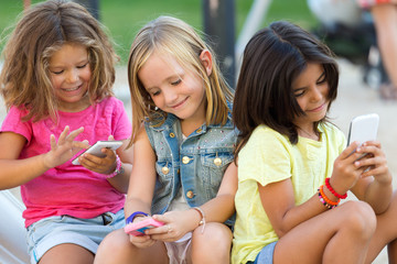 Group of childrens chatting with smart phones in the park.