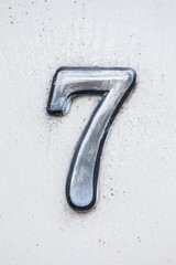 Metal digit - 7 on wooden background