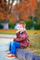 smiling boy in leather jacket and jeans