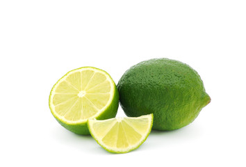Limes with slices and leaves isolated on white background