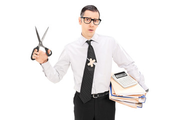 Accountant holding scissors and pile of documents