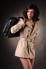 business woman wearing a raincoat and suitcase
