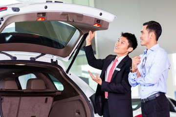 Asian man looking at car in dealership