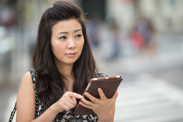 Young Asian Woman using tablet pc on city street
