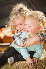 Little Boy Playing with His Baby Sister at Pumpkin Patch