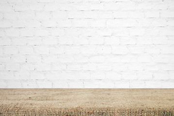 Sackcloth over table and white brick wall, background, template