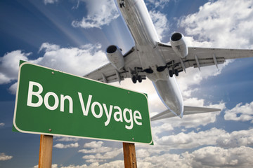 Bon Voyage Green Road Sign and Airplane Above