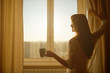 Woman in the morning by window. Attractive sexy woman with cup