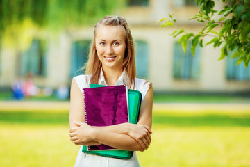 Student woman is standing with the folder and copy-book outdoors