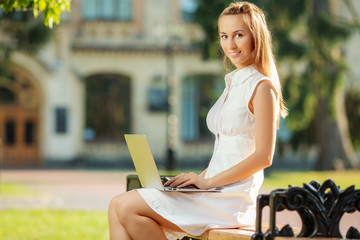 Beautiful student woman is using a laptop and sitting on a bench