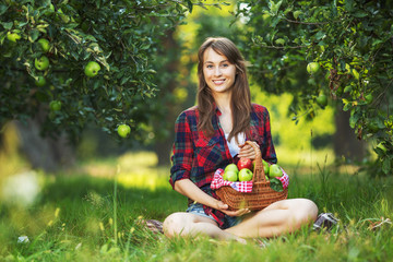 Beautiful woman with basket apples relaxing in a garden.