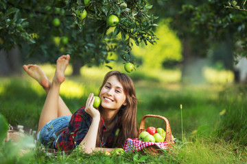 Woman with basket of apples relaxing in a garden.