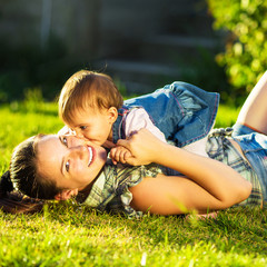 Mother and baby daughter are playing outdoors in summer
