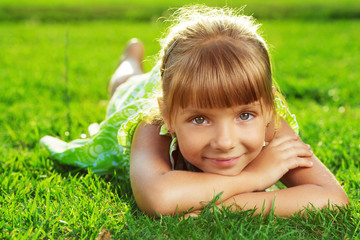Cute smiling little girl lying on a green grass in summer park