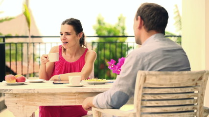 Couple talking on cellphone, drinking coffee on terrace