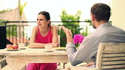 Young couple arguing, fighting by the table on terrace