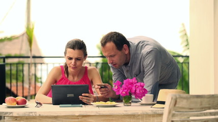 Young couple doing online shopping on tablet computer on terrace