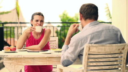 Happy couple chatting, drinking coffee by the table on terrace