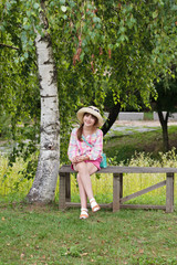 Happy girl sitting on a wooden bench near the birch tree