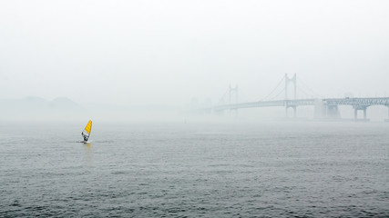 Misty landscape with river, bridge and yellow sail