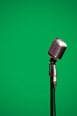 Stylish retro microphone on a green background