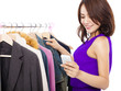 Happy asian Woman shopping clothes with a mobile phone  over whi