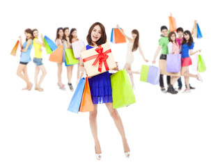 happy woman holding a gift box and color bags