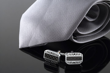 Tie with cuff links on background
