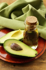 oil of avocado and fresh fruit on wooden table