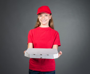 Pizza girl in red uniform delivering pizza isolated on grey.