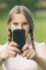 teenage girl taking photo with smartphone
