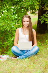 Teen girl works with the laptop on the grass near the tree
