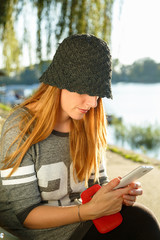 Young beautiful redhead girl using mobile phone beside the river