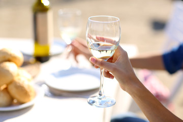 Friends enjoying drink at outdoor restaurant. Hand with glass,
