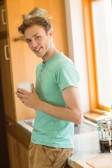 Young man smiling at camera holding coffee