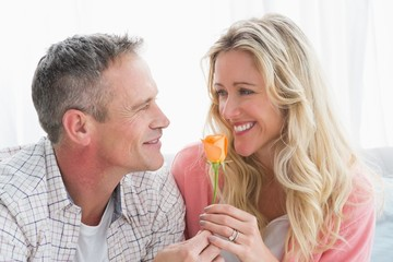 Happy woman smiling at partner who has given her a rose
