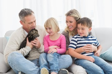 Happy family sitting with pet kitten together