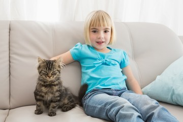 Little girl sitting on the couch stroking her cat
