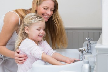Happy mother and daughter washing hands