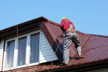 roofer builder worker spraying paint on roof