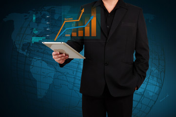 businessman holding a tablet showing business graph on virtual s