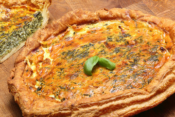 Tart with spinach on wooden background