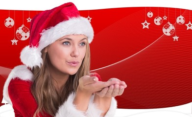 Composite image of festive blonde blowing over hands