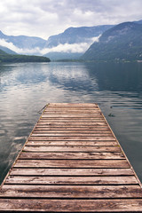Jetty on the misty lake in Alps, Austria