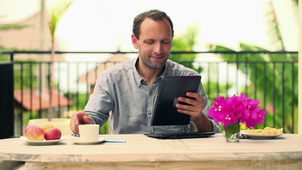 Young man with tablet computer sitting by the table on terrace