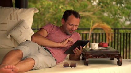 Young man with tablet computer relaxing on gazebo bed