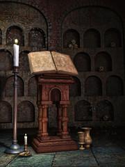 Stara księga i świece w krypcie z czaszkami